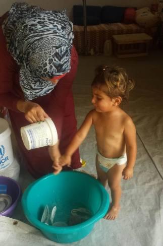 Qamar preparing to bathe Minas...